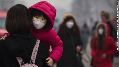 A Chinese girl wears a mask to protect against pollution as she is carried in a shopping district in heavy smog on December 8, 2015 in Beijing, China.