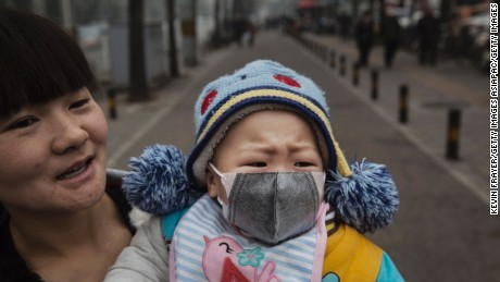 "BEIJING, CHINA - DECEMBER 08:  A Chinese girl wears a mask as she is held by her mother outside a local hospital during a day of heavy smog on December 8, 2015 in Beijing, China. The Beijing government issued a ""red alert"" for the first time since new standards were introduced earlier this year as the city and many parts of northern China were shrouded in heavy pollution. Levels of PM 2.5, considered the most hazardous, crossed 400 units in Beijing, lower than last week, but still nearly 20 times the acceptable standard set by the World Health Organization. The governments of more than 190 countries are meeting in Paris to set targets on reducing carbon emissions in an attempt to forge a new global agreement on climate change.  (Photo by Kevin Frayer/Getty Images)"