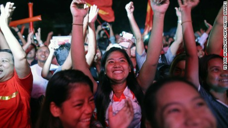 Supporters of Myanmar opposition leader Aung San Suu Kyi's party cheer as they watch results come in after the country's first democratic election in a generation.