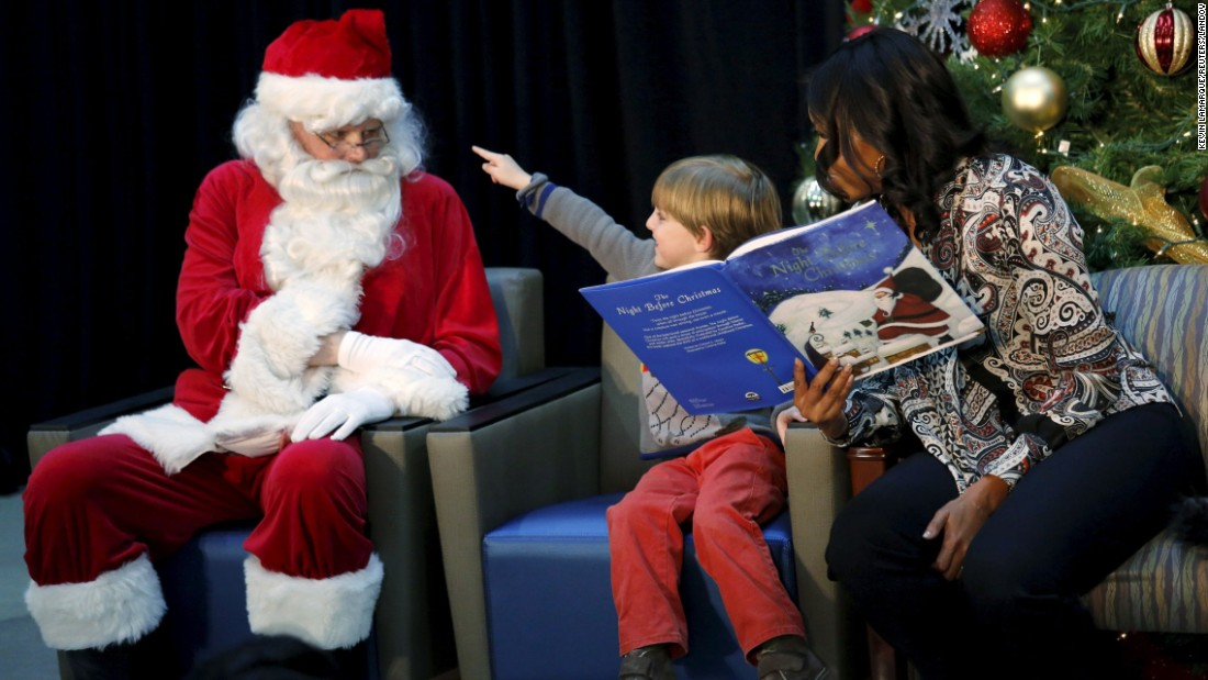 "Stephen Orzechowski, 6, points to Santa Claus as first lady Michelle Obama reads ""The Night Before Christmas"" to children in Washington on Monday, December 14."