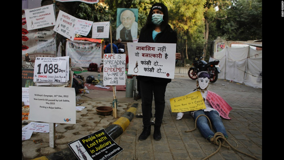 "An Indian woman holds a placard which reads, ""He is not a juvenile but a rapist, hang him"" on Wednesday, December 16, during a demonstration to commemorate the third anniversary of the fatal 2012 rape."