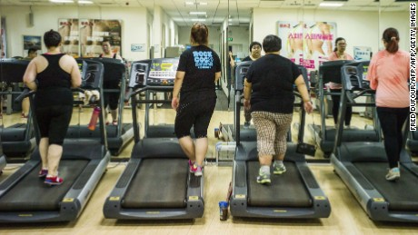 People walk on treadmills in a gymnasium.