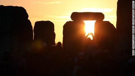 AMESBURY, ENGLAND - DECEMBER 21:  A man takes a photograph of the sunrise as druids, pagans and revellers celebrate the winter solstice at Stonehenge on December 21, 2012 in Wiltshire, England. Predictions that the world will end today as it marks the end of a 5,125-year-long cycle in the ancient Maya calendar, encouraged a larger than normal crowd to gather at the famous historic stone circle to celebrate the sunrise closest to the Winter Solstice, the shortest day of the year.  (Photo by Matt Cardy/Getty Images)