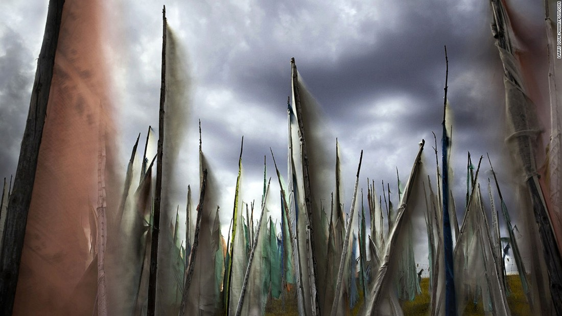 "Canadian Larry Louie traveled to the Tibetan Tagong grasslands of Sichuan province to capture prayer flags fluttering under leaden skies. His image was selected as winner in the ""colors of the world"" category. (Photo: Larry Louie/www.tpoty.com)"