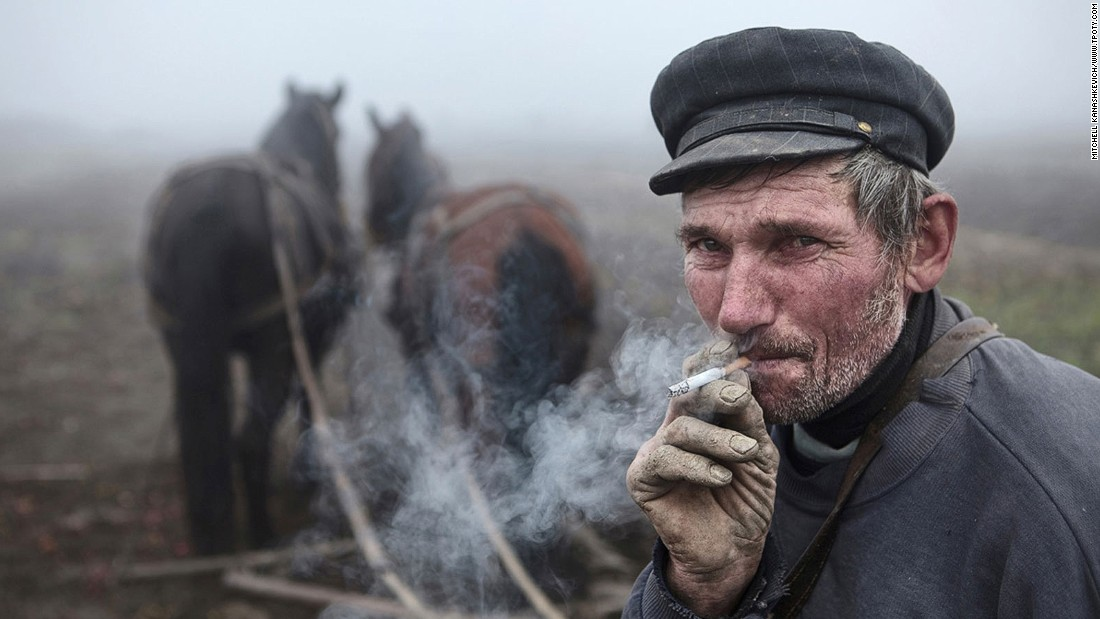 "A timeless image that could've been taken anywhere across rural Europe, anytime over the past century, earns Australian Kanashkevich Mitchell the top prize in the ""faces, people, encounters"" category. His photo shows a Hungarian-Romanian man taking a break from plowing a field in Maramures, Romania. (Photo: Kanashkevich Mitchell/www.tpoty.com)"