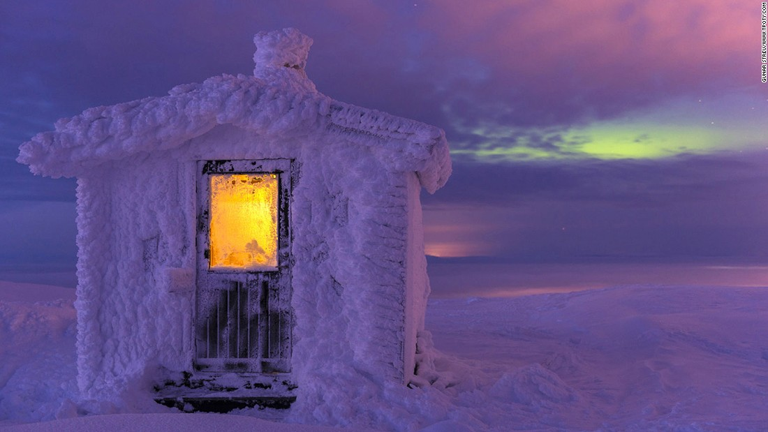 "The warm, rich colors don't detract from the obvious chill factor in this image by Germany's Gunar Streu, which was commended in the ""moment of light"" category. The photo shows a cabin covered in hoar frost in the Dundret nature reserve, Swedish Lapland, as northern lights illuminate the dusk sky. (Photo: Gunar Streu/www.tpoty.com)"