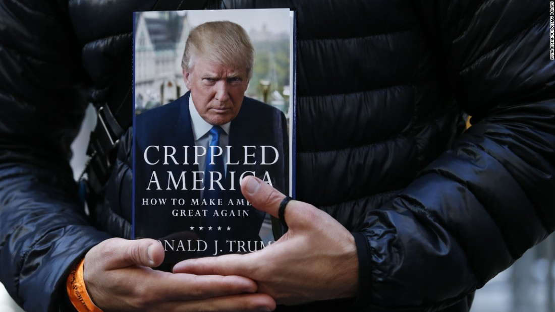 "A man holds a copy of Trump's newest book, ""Crippled America: How to Make America Great Again,"" while he waits to have it signed by Trump outside Trump Tower in New York on November 3."