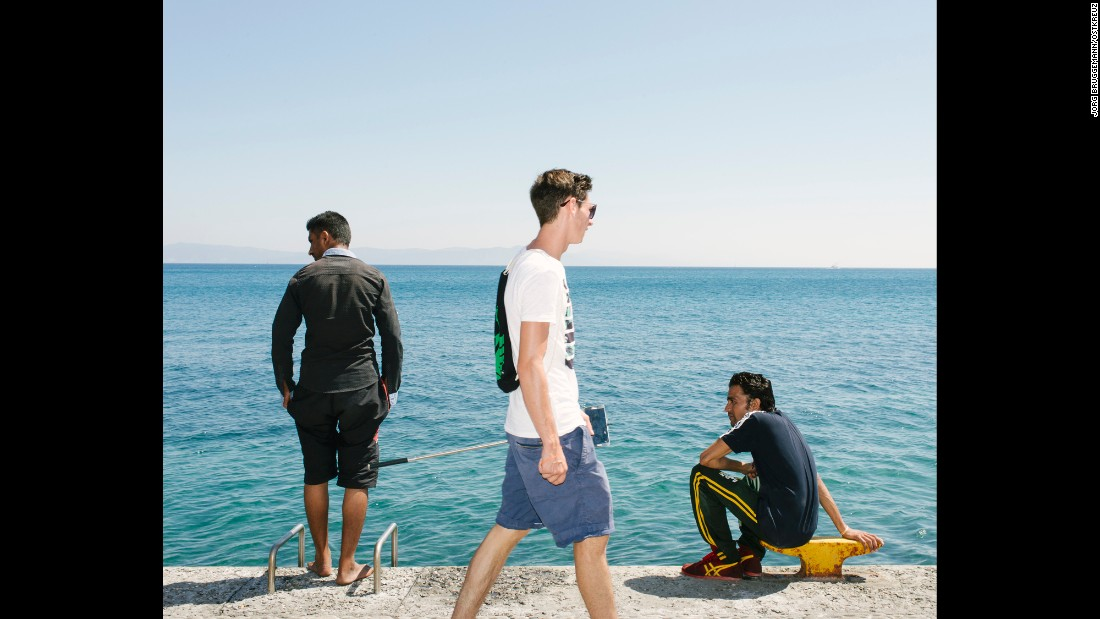 A German tourist, with selfie stick in hand, walks past migrants on the beach promenade.