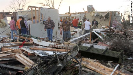 People inspect a storm-damaged home in the Roundaway community near Clarksdale, Mississippi, on Wednesday.