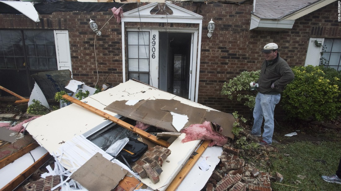 Michael Downard stands outside his house in Rowlett the morning after it was struck by a tornado.