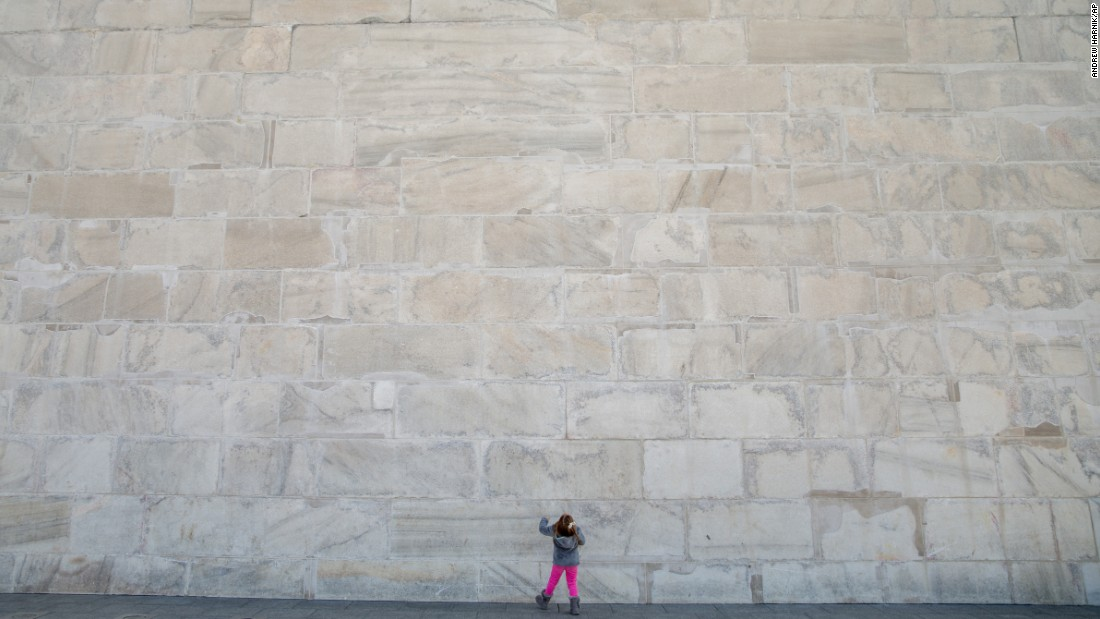 Photos of the U.S. capital's Washington Monument sometimes fail to capture the scale of the obelisk which opened to the public 127 years ago. This young girl, photographed at the foot of the 169-meter (555 foot), structure, gives some sense its size.