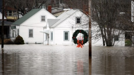 A holiday wreath hangs from a light post surrounded by floodwater from the Bourbeuse River, Tuesday, Dec. 29, 2015, in Union, Mo. Flooding across Missouri has forced the closure of hundreds of roads and threatened homes. (AP Photo/Jeff Roberson)