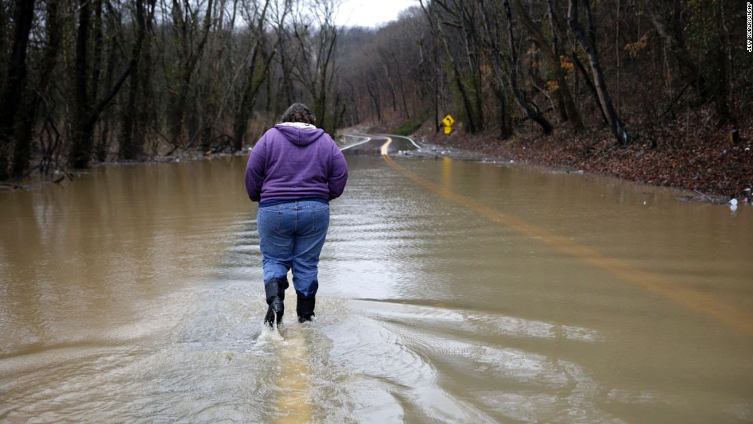 A woman walks down a flooded road to get back to her home in Eureka, Missouri, before evacuating on December 28.
