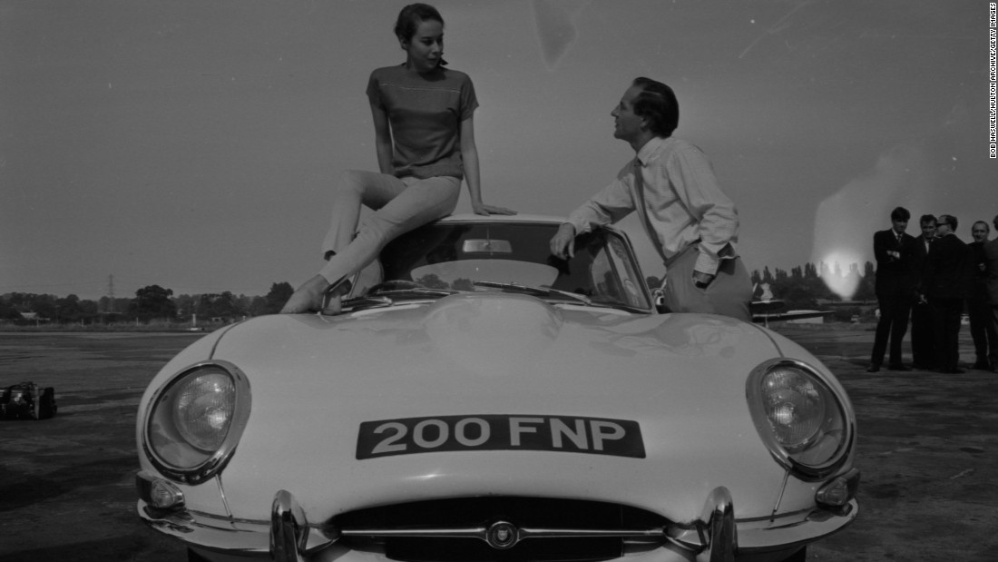 An icon of the Swinging Sixties arrives with the E-Type Jaguar, seen here with racing driver Innes Ireland and Kathy Keeton.