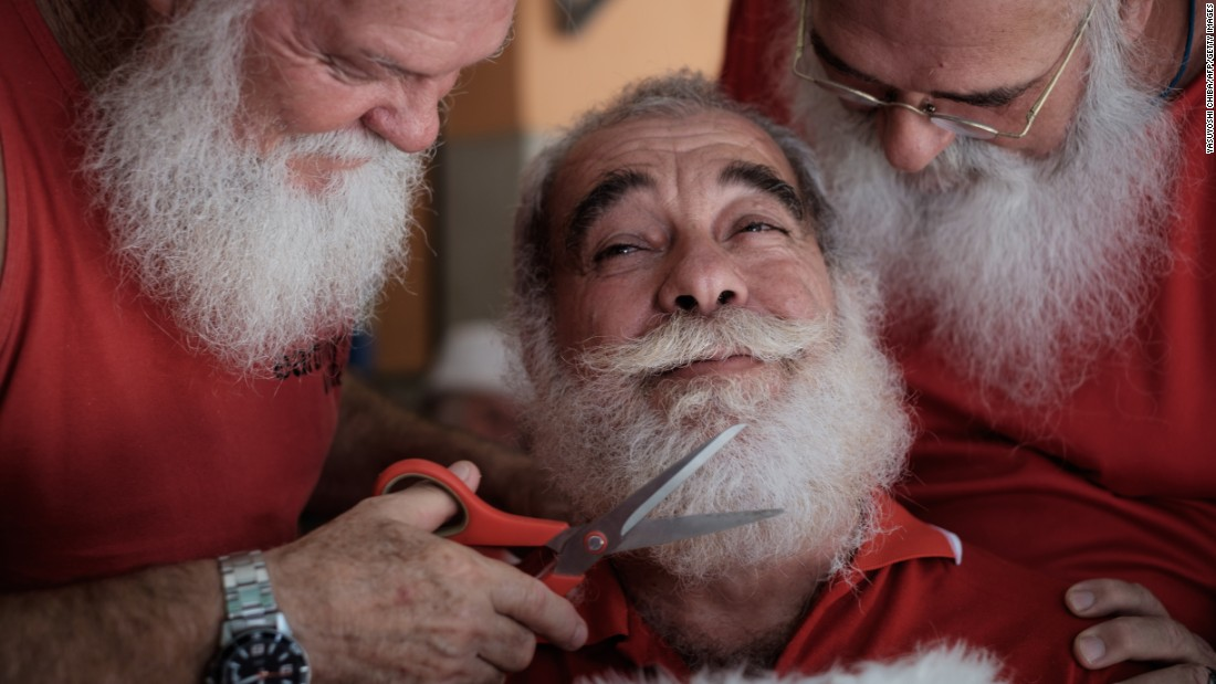 A graduate of Brazil's School of Santa Claus gets his beard trimmed by students in Rio de Janeiro on Monday, December 28. The school prepares men to represent Santa Claus during the Christmas season.