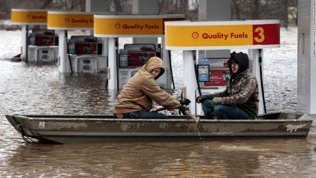"Men row a boat past a gas station near Fenton, Missouri, on Wednesday, December 30. Torrential rains in the state have pushed <a href=""http://www.cnn.com/2015/12/30/us/gallery/midwest-flooding/index.html"" target=""_blank"">swollen rivers and streams</a> to new heights."