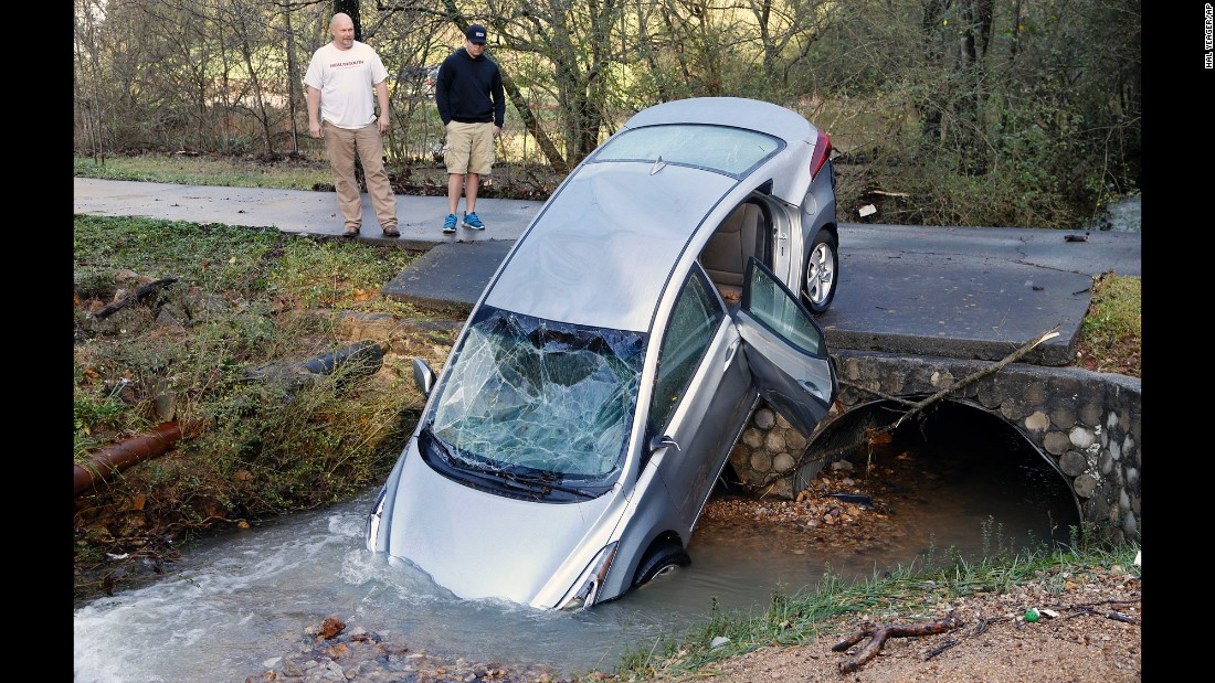 A man and his son look at a vehicle that wound up in the culvert of their driveway after floodwaters swept it and its four occupants off the road Friday, December 25, in Pinson, Alabama. The car's occupants had to be rescued by the fire department.