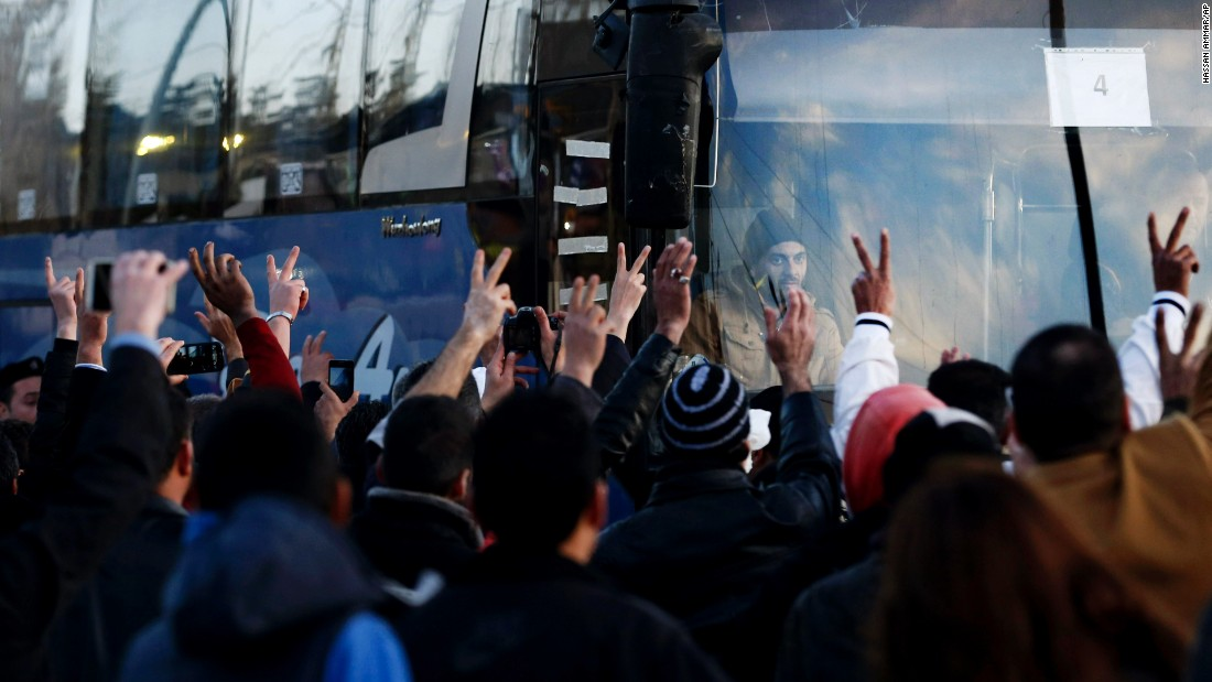 Syrian and Lebanese people wave and flash victory signs as convoys carrying wounded Syrian opposition fighters leave the Lebanese border crossing point of Masnaa on Monday, December 28. The fighters will be flown to Turkey as part of a U.N.-backed truce deal reached in September.