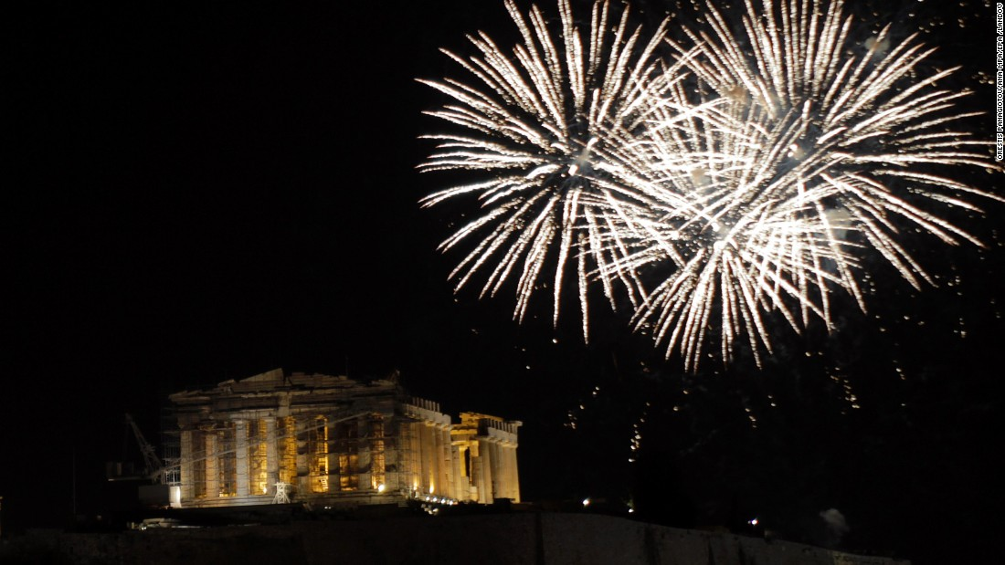 Fireworks illuminate the sky over the hill of the Acropolis in Athens, Greece.