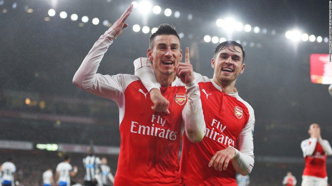 Laurent Koscielny (L) of Arsenal celebrates scoring against Newcastle United with team mate Aaron Ramsey (R).