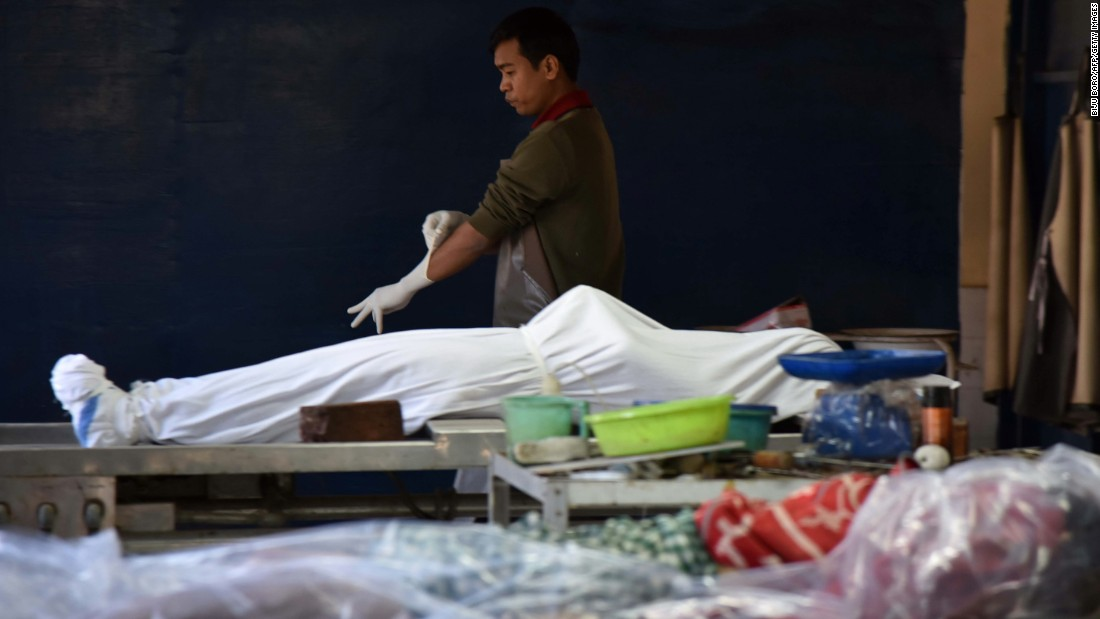 A hospital worker stands next to a body in Imphal on January 4.