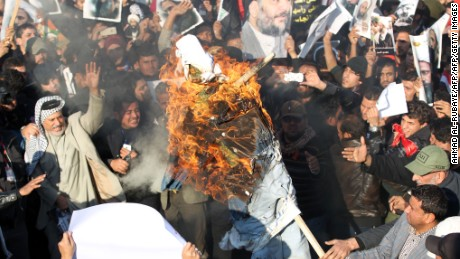 Supporters of Iraqi Shiite cleric Moqtada al-Sadr (portrait top-C) burn a effigy of a member of the Saudi ruling family as others hold posters of prominent Shiite cleric Nimr al-Nimr during a demonstration in the capital Baghdad on January 4, 2016, against Nimr's execution by Saudi authorities. Sunni-ruled Saudi Arabia severed diplomatic ties with Shiite-dominated Iran, its long-time regional rival, after angry demonstrators attacked the Saudi embassy in Tehran and its consulate following Nimr's execution. AFP PHOTO / AHMAD AL-RUBAYE / AFP / AHMAD AL-RUBAYE        (Photo credit should read AHMAD AL-RUBAYE/AFP/Getty Images)