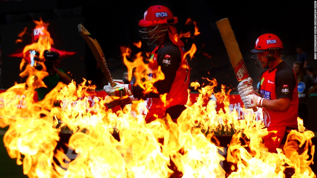 Cricketers Chris Gayle, center, and Aaron Finch walk through flames before a Big Bash League match in Melbourne on Wednesday, December 30. Gayle and Finch play for the Melbourne Scorchers.