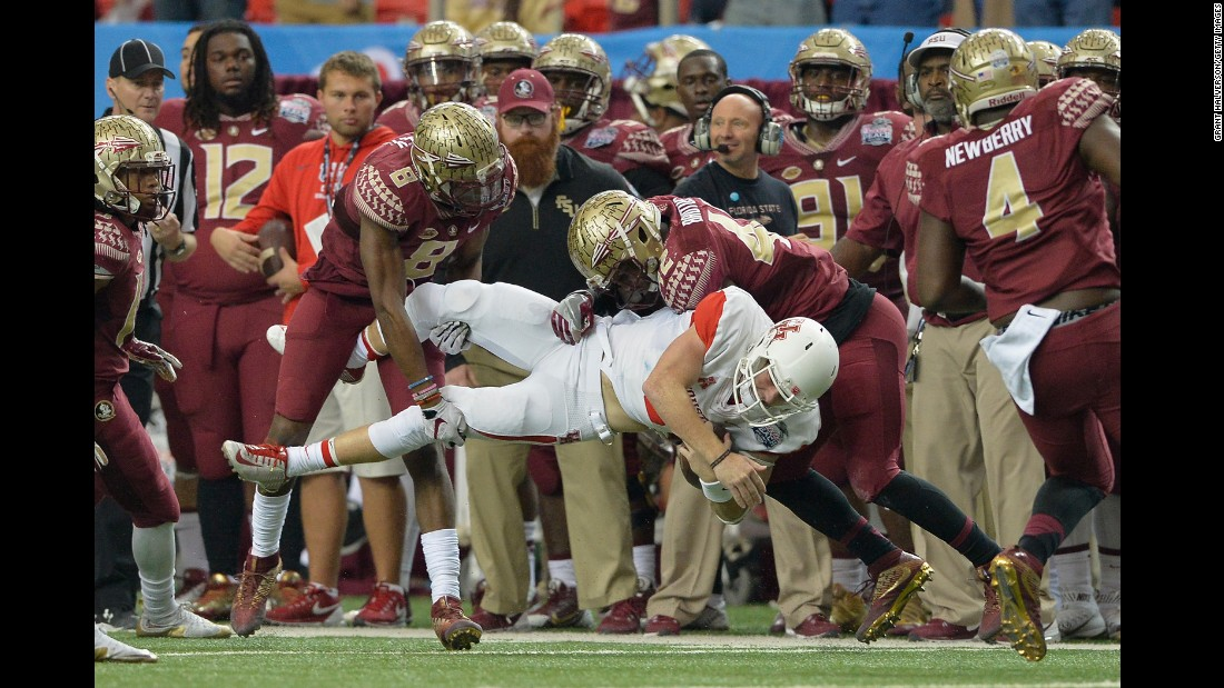 Houston quarterback Kyle Postma is tackled by Florida State's Jalen Ramsey (No. 8) and Lamarcus Brutus during the Peach Bowl in Atlanta on Thursday, December 31.