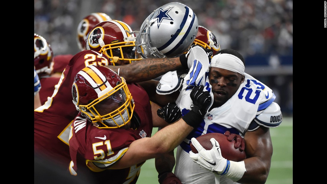 Dallas' Robert Turbin loses his helmet as he's crunched by Washington Redskins on Sunday, January 3. A personal foul was called on the play.