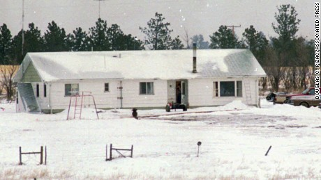 An unidentified man appears to point a rifle from the open door of Justus Township headquarters for the freemen group, some 30 miles outside Jordan, Montana, on March 27, 1996.