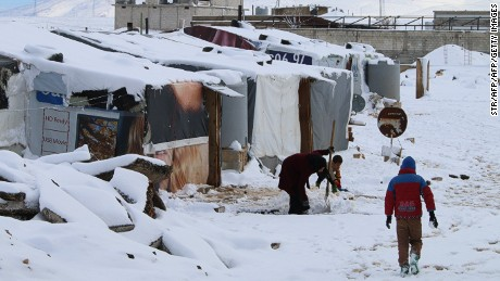 Syrian refugees walk in a makeshift camp in Lebanon last year.