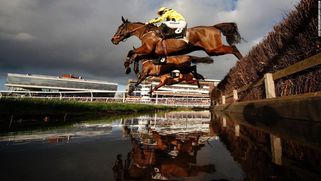 Horses clear a water jump during a steeplechase race in Newbury, England, on Tuesday, December 29.