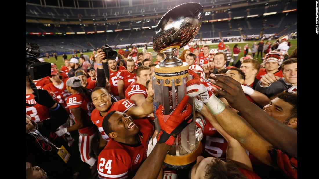 Wisconsin football players hold up the Holiday Bowl trophy after defeating USC on Wednesday, December 30.