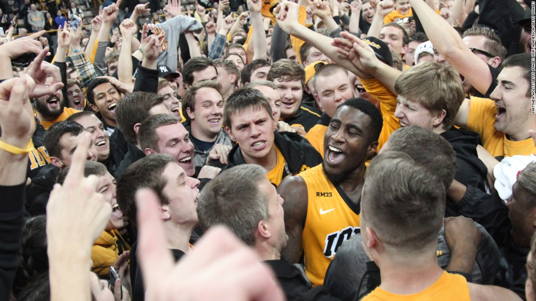 Iowa guard Anthony Clemmons, center, celebrates with fans who stormed the court after the Hawkeyes upset No. 1 Michigan State on Tuesday, December 29. It was Michigan State's first loss of the season.