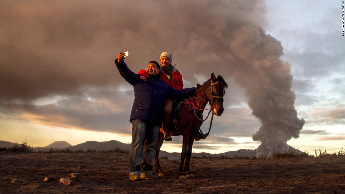 Tourists take a selfie as Mount Bromo erupts in Probolinggo, Indonesia, on Thursday, December 31.