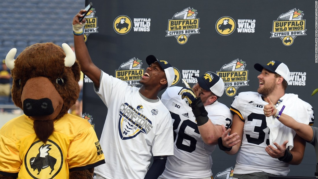 Michigan wide receiver Jehu Chesson takes a selfie with his teammates after they won the Citrus Bowl in Orlando on Friday, January 1.