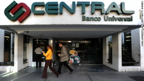 "A couple walks in front of the Central bank in Caracas, on December 04, 2009. Venezuela's government has closed three more banks for inspection, the country's finance minister said Friday, amid a rash of nationalizations that has spooked investors. Ali Rodriguez said the banks were undergoing a ""closed-door"" inspection for ""rehabilitation"" days after a similar move led to the nationalization of four other banks.   AFP PHOTO/Juan Barreto (Photo credit should read JUAN BARRETO/AFP/Getty Images)"