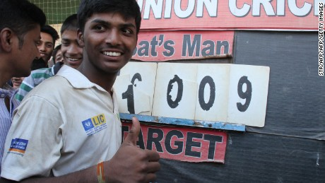 Pranav Dhanawade, 15, poses next to the score board after smashing a 117-year-old record for the number of runs scored in one innings.