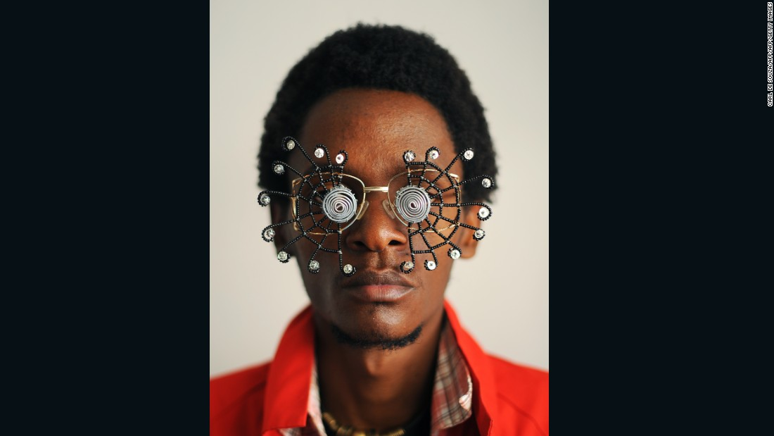 "Kabiru created thrifty artworks made from found objects for his ""C-Stunners"" series. Here, he poses with one of his creations. The series is inspired by his father, who once fell out of love with his own spectacles after receiving a beating from his parents for breaking them."