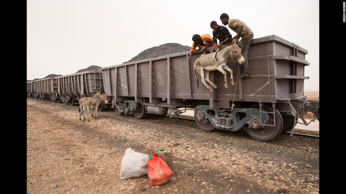 A donkey is loaded onto a train filled with iron ore in the West African country of Mauritania. Photographer George Popescu rode the train last fall -- a 40-hour round-trip journey through the Sahara desert.