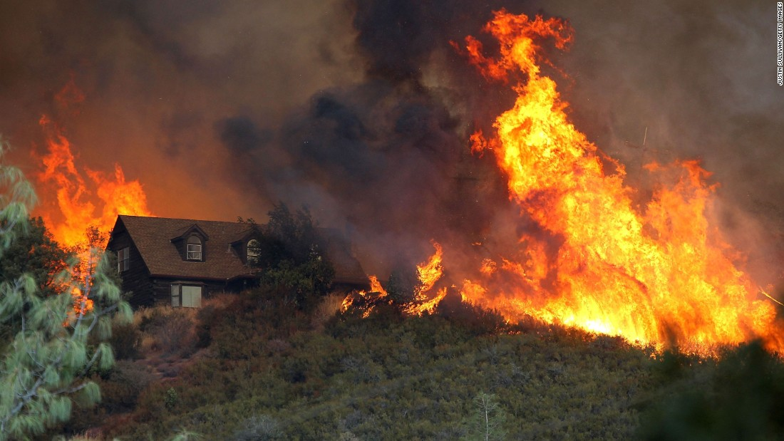 Flames from the Rocky Fire approach a house on July 31 in Lower Lake, California. Wildfires burned more than 10 million acres in the United States during 2015, the most on record and 40% more than in an average year.