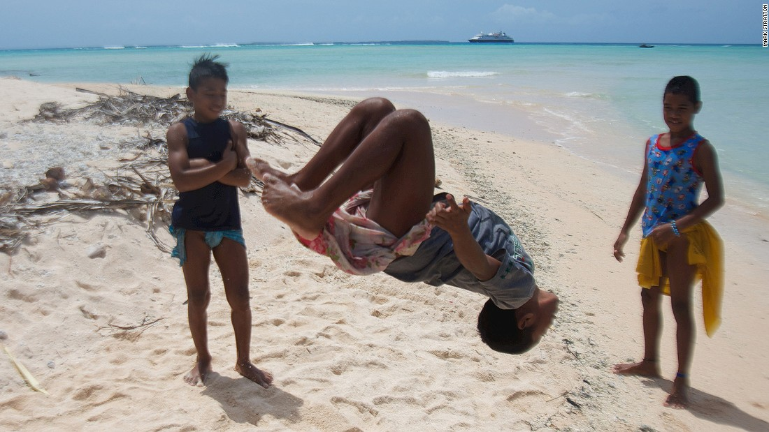 Micronesia's 607 islands are home to a vanishing way of life. Pulap Atoll's children show off their acrobatic prowess while the author's cruise ship waits outside the barrier reef.