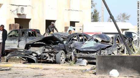 Libyan onlookers inpect damaged cars at the site of a suicide truck bombing on a police school in Libya's coastal city of Zliten, some 170 kilometres (100 miles) east of the capital Tripoli, which killed at least 50 people on January 7, 2015, in the deadliest attack to hit the strife-torn country since its 2011 revolution. AFP PHOTO / MAHMUD TURKIA / AFP / MAHMUD TURKIA        (Photo credit should read MAHMUD TURKIA/AFP/Getty Images)