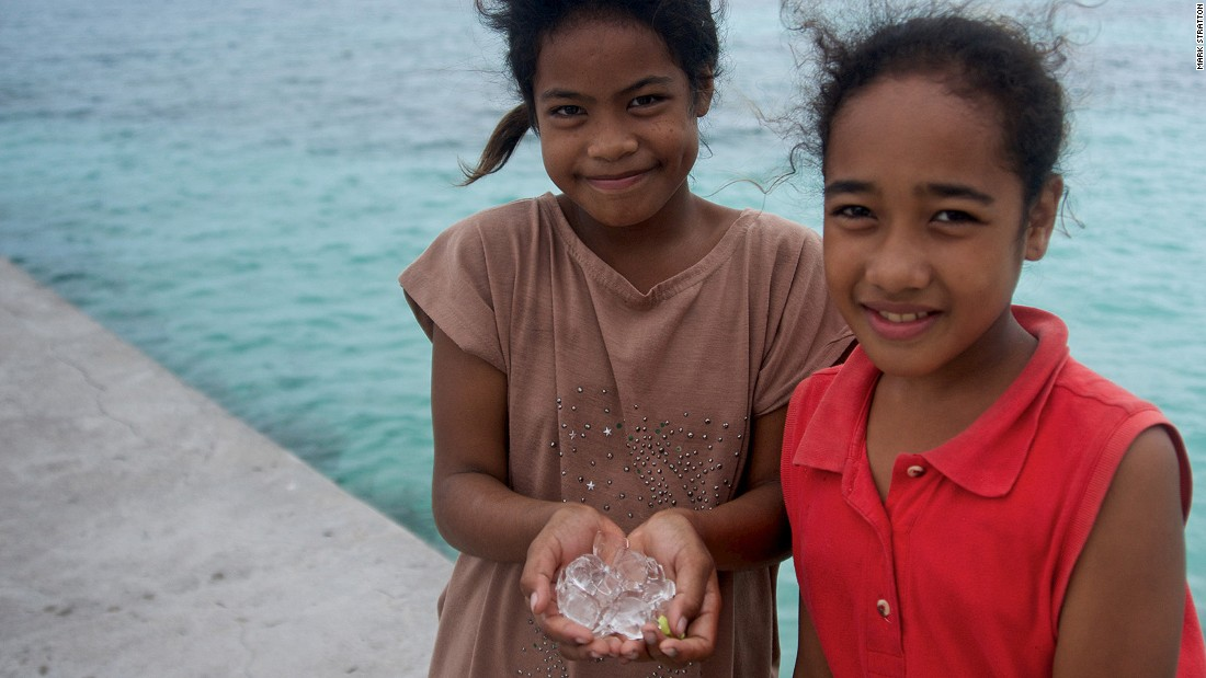 With no refrigeration on Kapingamarangi Atoll, children are fascinated by ice cubes brought ashore by the crew of expedition cruise ship Silver Discoverer.