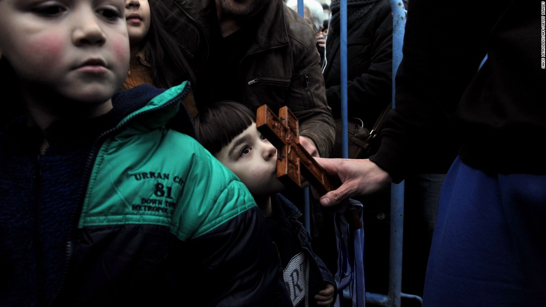 A child in Thessaloniki, Greece, kisses a wooden cross during a ceremony marking the Epiphany holiday on Wednesday, January 6.