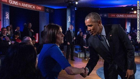 "US President Barack Obama greets Taya Kyle, widow of Navy Seal Chris Kyle, made fampous by the film ""American Sniper,"" during a commercial break at a town hall meeting with CNN's Anderson Cooper on reducing gun violence at George Mason University in Fairfax, Virginia, on January 7, 2016."