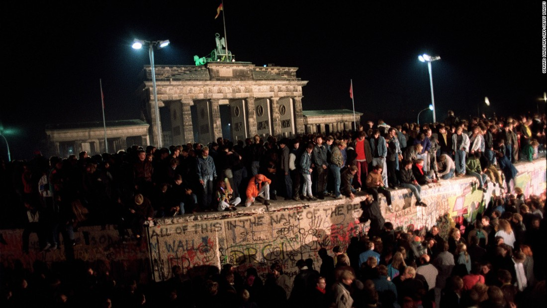 On November 11, 1989, thousands of young East Berliners gather at the Berlin Wall near the Brandenburg Gate as they wait for a crossing into the West to be opened. The fall of East Germany meant the end of life as BFC had known it.