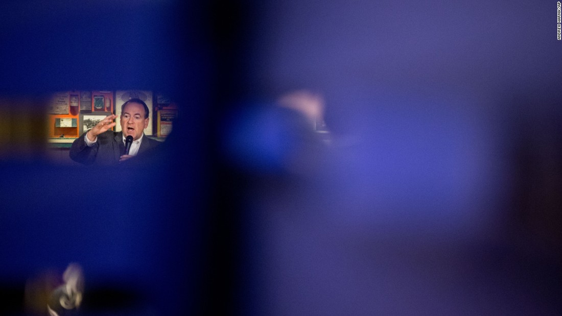 Republican presidential candidate Mike Huckabee is seen through wall slats as he speaks in Urbandale, Iowa, on Sunday, January 3. Caucuses in Iowa are set for February 1.