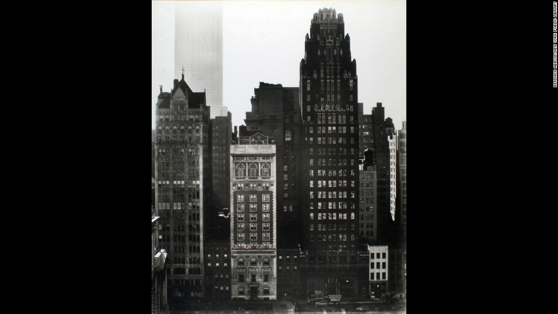 Further south, from across Bryant Park on 40th Street, Abbott photographed the Scientific American and American Radiator buildings in 1935. The Empire State Building looms in the background.
