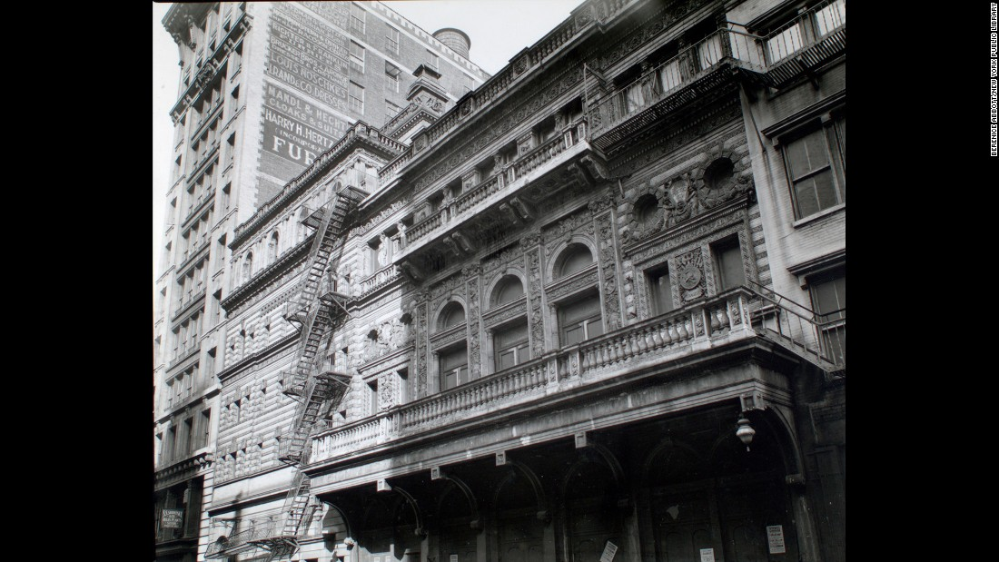 Twelve blocks south, the ornate Fifth Avenue Theater sits on Broadway in 1938. On the building next door, advertisements promote fur and clothing.